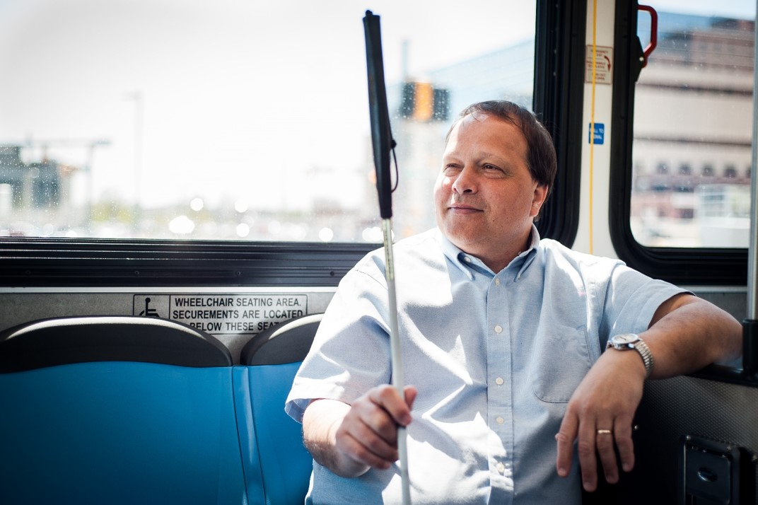 Man with cane on bus