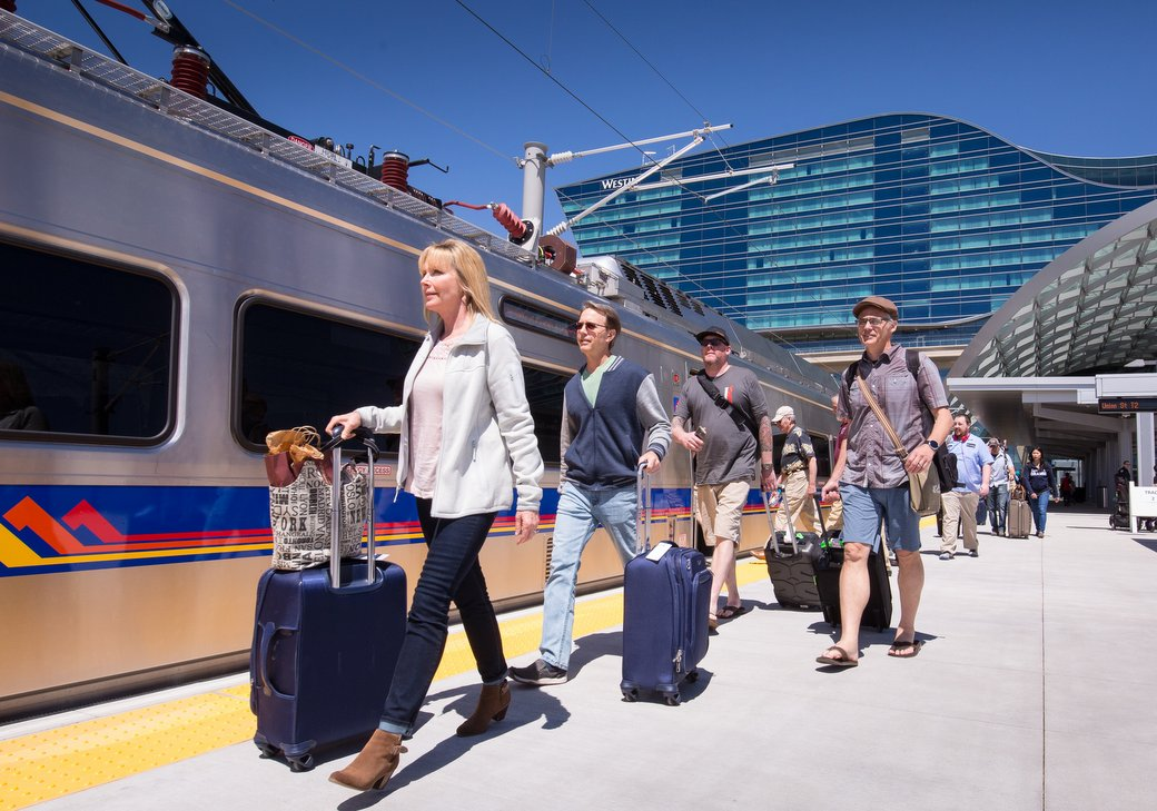 Passengers with suitcases board RTD commuter rail train outside Denver International Airport