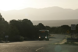 A photo of a transit vehicle driving through mountainous rural terrain.