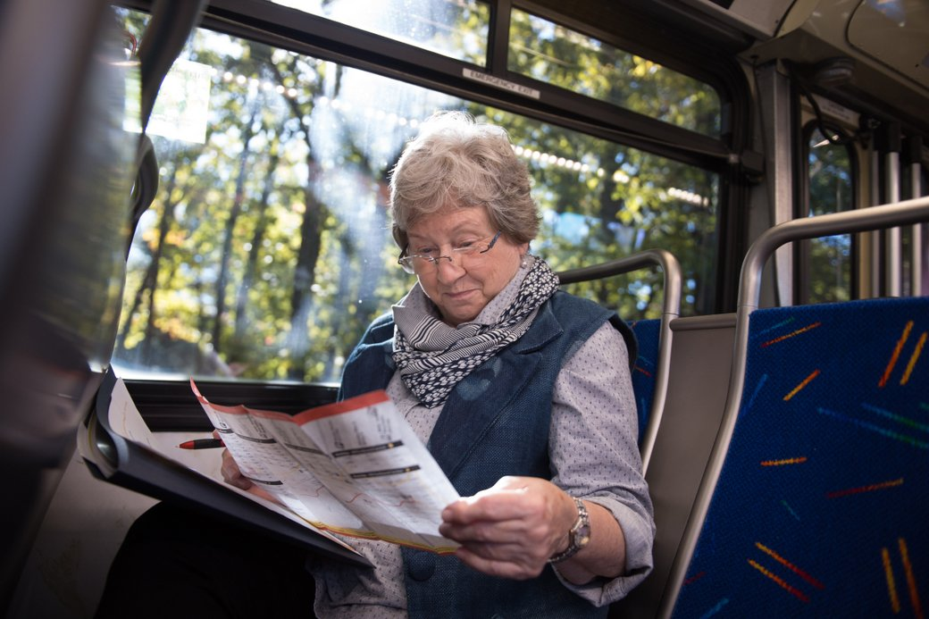 Older adult consults map while on subway